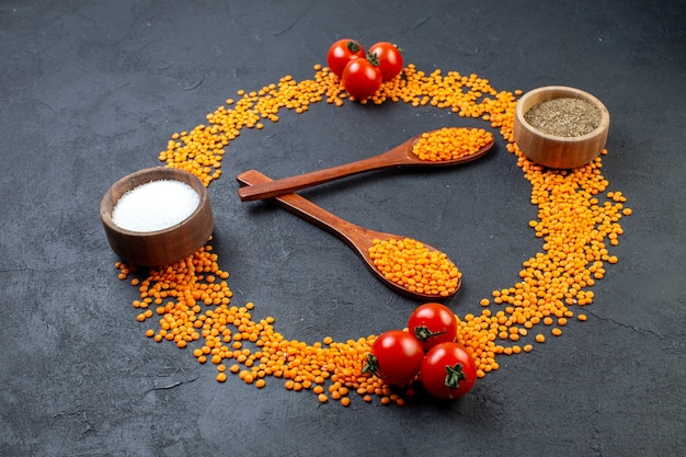 Front view of red lentils lined up in a circle and tomatoes pepper salt on black background