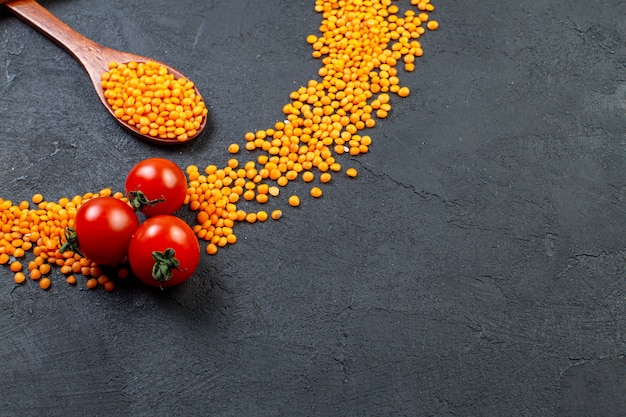 Front view of red lentils and tomatoes on black background with free space