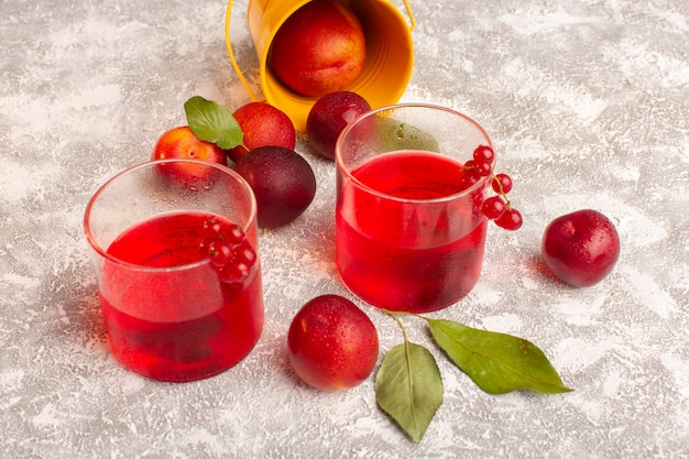 Front view red plum juice with fresh plums on bright fruit color juice drink