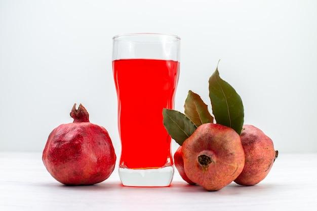 正面図白い表面に新鮮なザクロが入った赤いザクロジュース