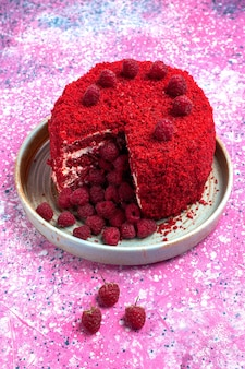Front view red raspberry cake baked delicious inside plate on pink desk.