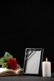 Vista frontale della rosa rossa con libro e cornice su nero