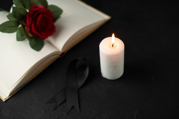 Front view of red rose with open book and candle on black
