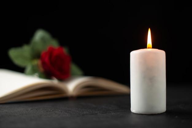 Vista frontale della rosa rossa con libro aperto e candela su nero