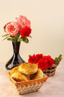 Una vista frontale rose rosse un bel colore rosa e fiori all'interno della brocca nera insieme a qogals all'interno del cestino del pane isolato sul tavolo e sul rosa