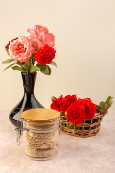 A front view red roses beautiful pink and red flowers inside black jug along with crisps isolated on pink