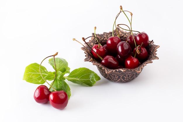 Вид спереди красные вишни внутри коричневой тарелки на белом