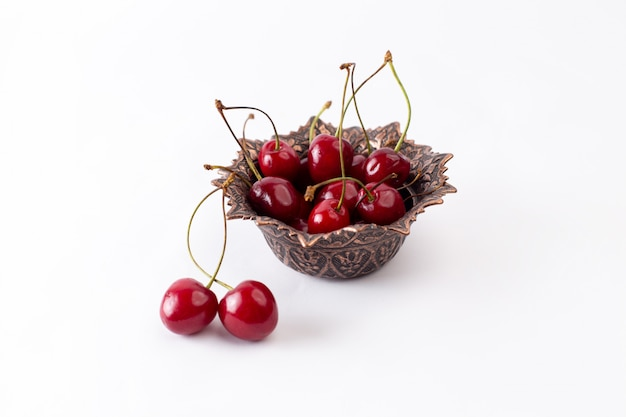 Вид спереди красная вишня внутри тарелки на сером