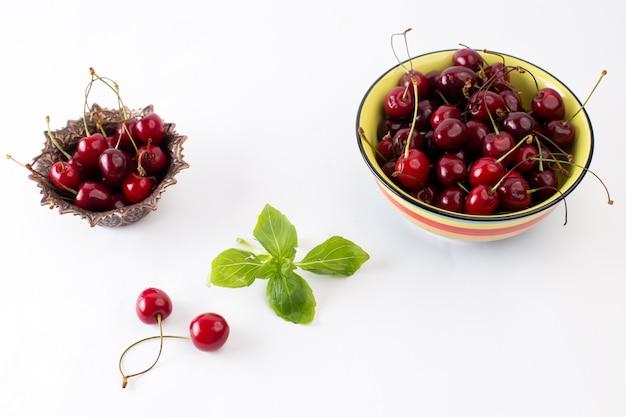 Красная вишня, вид спереди, внутри тарелок на белом