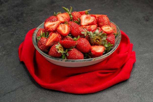 Vista frontale fragole rosse all'interno del piatto su sfondo scuro colore estivo succo di bacche selvatiche