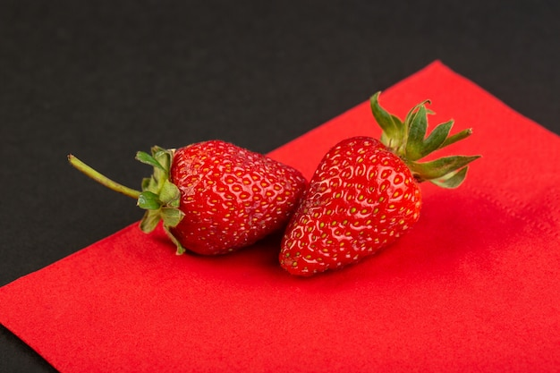 A front view red strawberries isolated mellow juicy on the red and black background berry textured