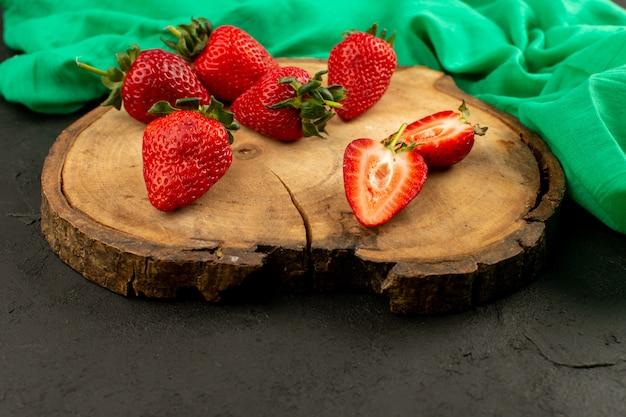 正面の赤いイチゴは、暗闇の中で茶色の机の上で熟した熟したスライス