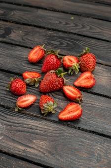 Vista frontale fragole rosse affettate e frutti interi su una scrivania rustica in legno scuro colore estivo bacche di succo di albero selvatico