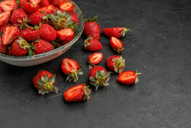 Front view red strawberries sliced and whole fruits on a grey background summer color wild tree  juice berry