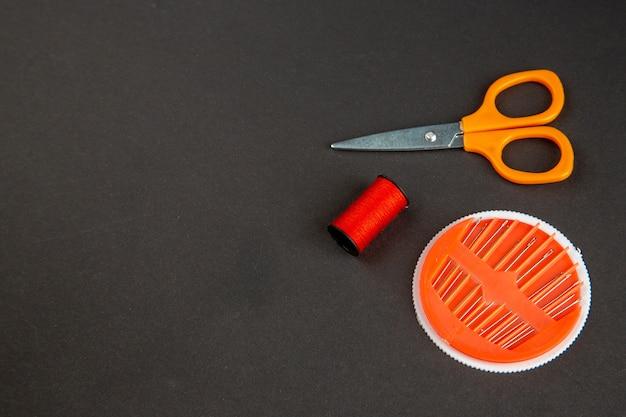 暗い背景にハサミと針で正面図の赤い糸