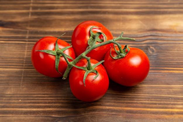 Вид спереди красные помидоры, спелые овощи на коричневом деревянном столе, красный спелый свежий диетический салат