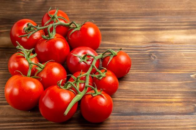 Вид спереди красные помидоры, спелые овощи на коричневом деревянном столе, красный салат, спелая свежая диета