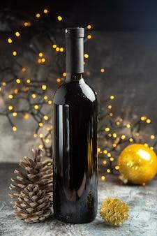 Vista frontale della bottiglia di vino rosso per la celebrazione e due coni di conifere su sfondo scuro