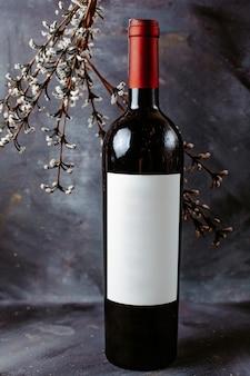 灰色の表面に正面の赤ワインのボトル