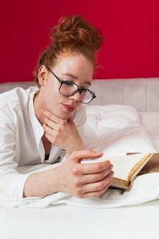 Front view redhead girl in bed reading