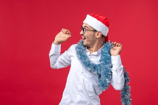赤い壁の人間のクリスマス休暇で新年を祝う正面図通常の男性