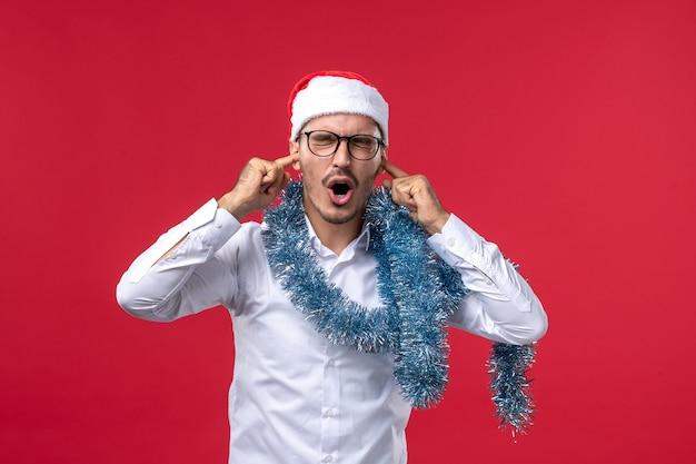 赤い壁のクリスマスの人間の休日に新年を祝う正面図通常の男性