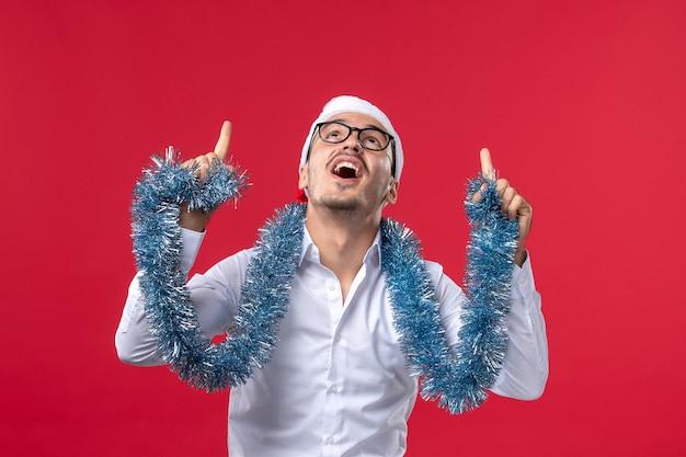 Maschio normale di vista frontale che celebra il nuovo anno sul natale umano di festa della parete rossa