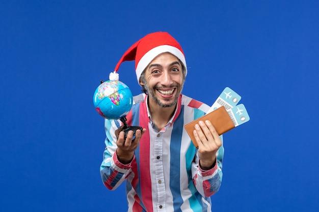 地球儀と青い床の感情の休日の新年のチケットを持つ正面図通常の男性