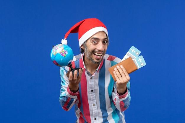 Вид спереди обычного мужчины с глобусом и билетами на синей стене эмоции праздника нового года