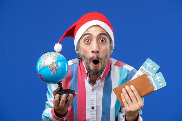 地球儀と青い壁の感情の休日新年のチケットを持つ正面図通常の男性