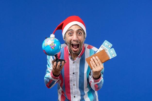 地球儀と青い壁の感情の休日の新年のチケットを持つ正面図の通常の男性