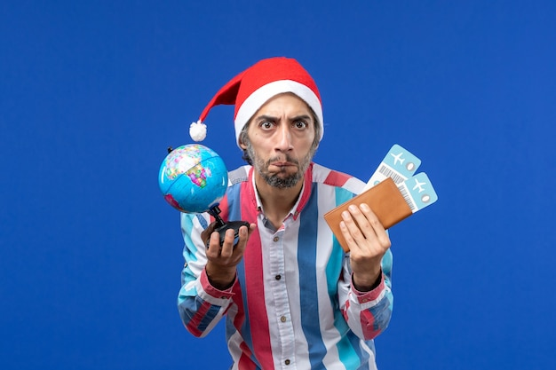 Front view regular male with globe and tickets on blue desk emotion holiday new year