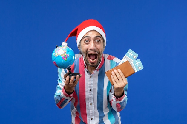 Front view regular male with globe and tickets on blue wall emotions holiday new year