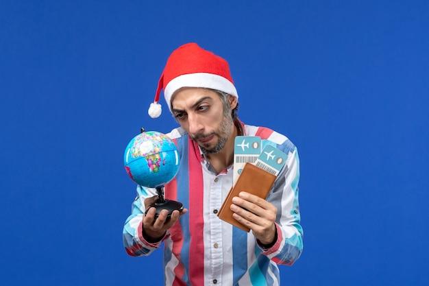青い壁の感情の休日の新年にチケットと地球儀を持つ通常の男性の正面図