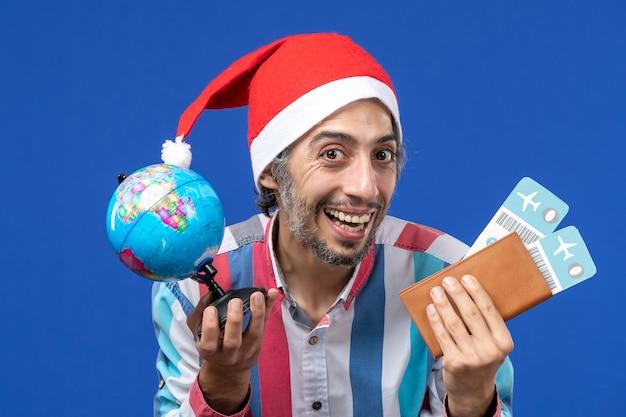 青い壁の感情の休日の新年のチケットと地球儀と正面図通常の男性