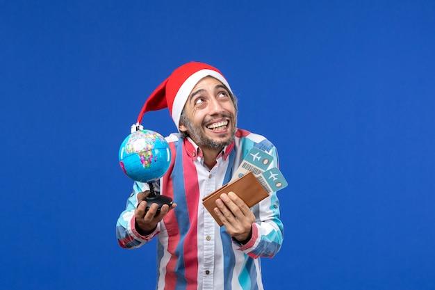 Вид спереди обычного мужчины с билетами и глобусом на синей стене праздничной эмоции новый год