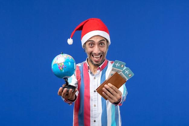 青い壁の休日の色の新年のチケットと地球儀と正面図通常の男性