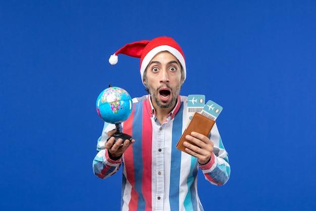 Maschio regolare di vista frontale con i biglietti e il globo sul colore blu di nuovo anno di festa della scrivania