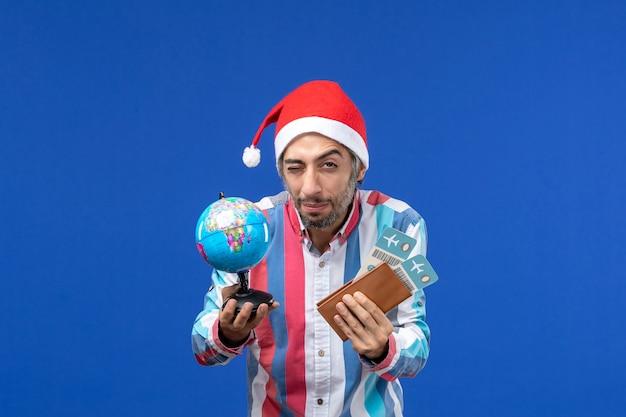 Maschio regolare di vista frontale con biglietti e globo sul nuovo anno di emozione di festa del pavimento blu