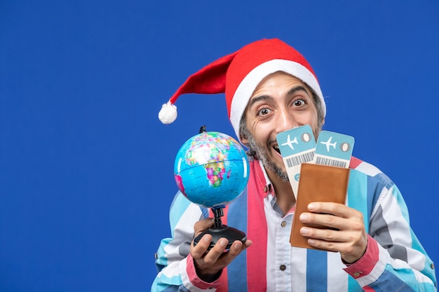 Front view regular male with tickets and globe on blue wall color holiday new year