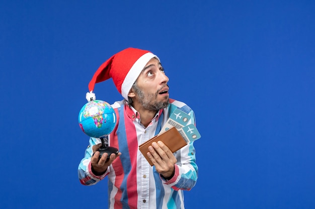 Front view regular male with tickets and globe on a blue wall holiday emotion new year