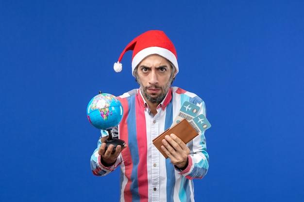 Maschio regolare di vista frontale con biglietti e globo su un nuovo anno di emozione di festa della parete blu