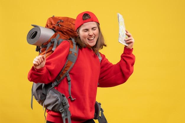 Vista frontale esultò escursionista femminile con zaino rosso che tiene mappa