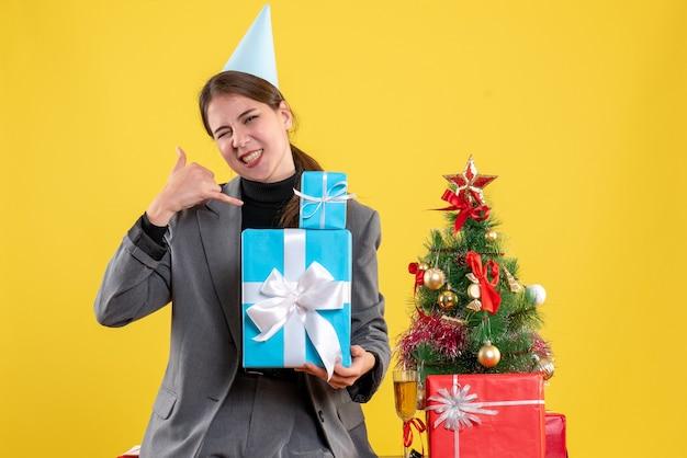 正面図は、クリスマスツリーとギフトカクテルの近くで私に電話ジェスチャーをさせるクリスマスギフトを保持しているパーティーキャップで喜んだ女の子