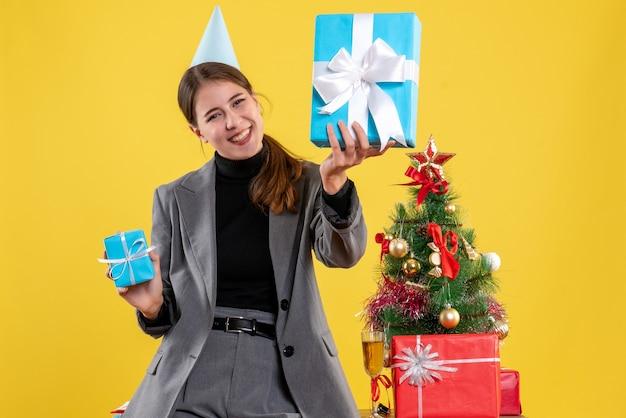 La vista frontale ha rallegrato la ragazza con la protezione del partito che tiene i regali di natale vicino all'albero di natale e al cocktail dei regali