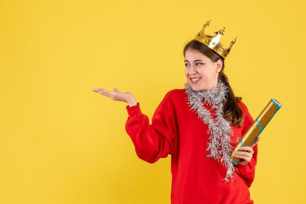빨간 스웨터를 들고 파티 포퍼를 손가락으로 가리키는 전면보기 기쁨 소녀