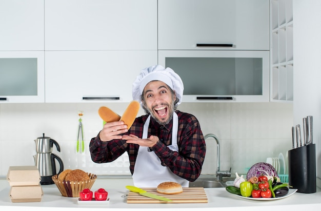 Front view of rejoiced male chef holding bread in the kitchen