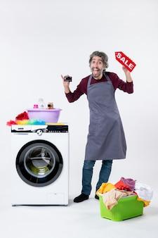 Vista frontale uomo rallegrato che regge la carta e il cartello di vendita in piedi vicino al cesto della biancheria della lavatrice sul muro bianco