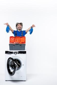 Vista frontale del riparatore gioito che tiene i guanti dietro la lavatrice sul muro bianco