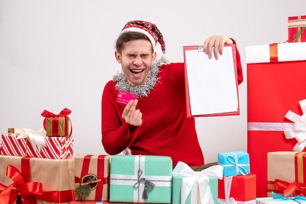 전면보기는 크리스마스 선물 주위에 앉아 카드와 클립 보드를 들고 젊은 남자를 기쁘게